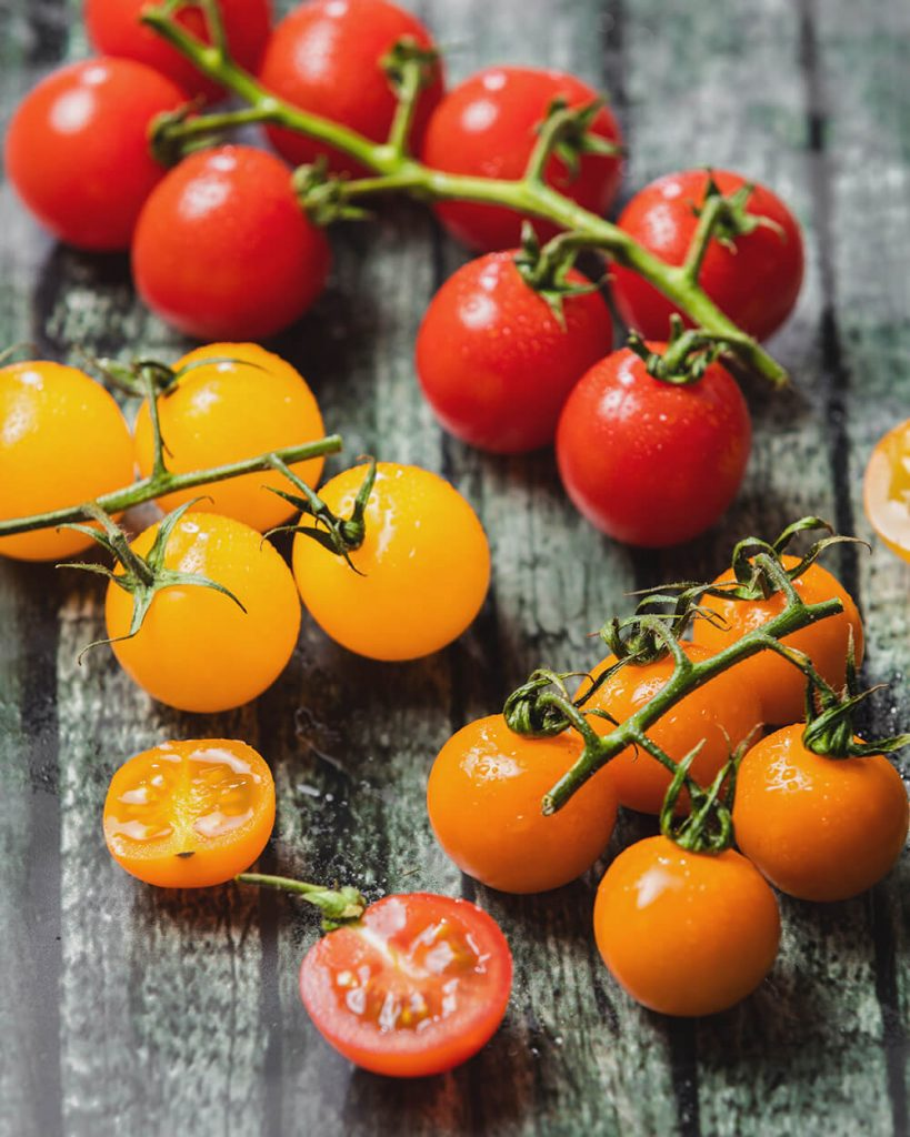 Mixed coloured tomatoes on vine